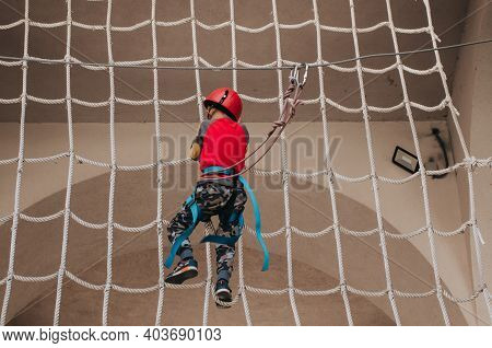 Boy In A Helmet Is Engaged In An Adventure Rope Park With All Climbing Equipment