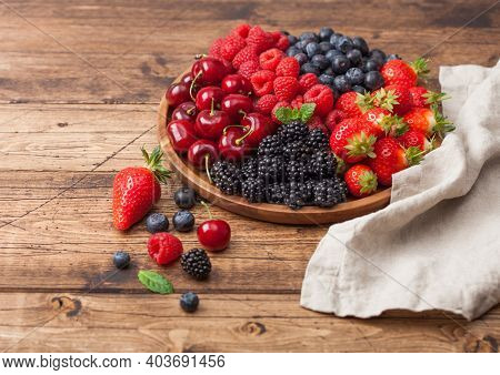 Fresh Organic Summer Berries Mix In Round Wooden Tray On Light Wooden Table Background. Raspberries,