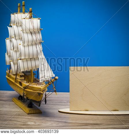 Souvenir Boat On A Blue Background. Wooden Frame With A Ship.