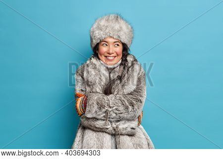 Photo Of Pretty Pleased Young Eskimo Woman Embraces Herself Feels Comfortable In Winter Coat And Hat