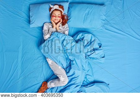 Photo Of Pleased Redhead Woman Sleeps With Eyes Closed Applies Beauty Hydrogel Patches Keeps Hands O