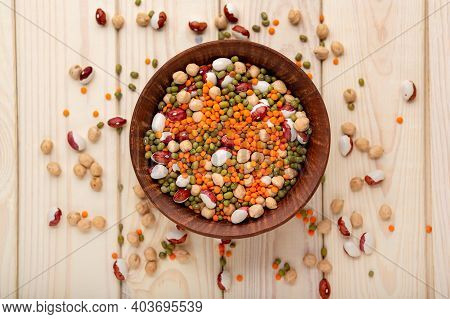 Assorted Raw Dry Legumes In Rustic Bowl Top View. White Beans, Lentils, Chickpeas, Kidney Beans. Mix