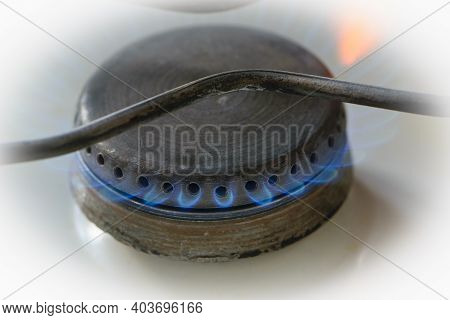 Blue Fire Burning Natural Gas On A Kitchen Gas Stove. Close-up. Steel Panel With Gas Ring Burner. Ma