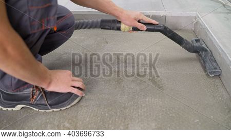 Cleaning Of Construction Waste With A Vacuum Cleaner. Worker Vacuuming Debris And Dust From Floor Af