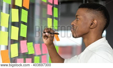 Concentrated African American Male Employee Managing Working Tasks.
