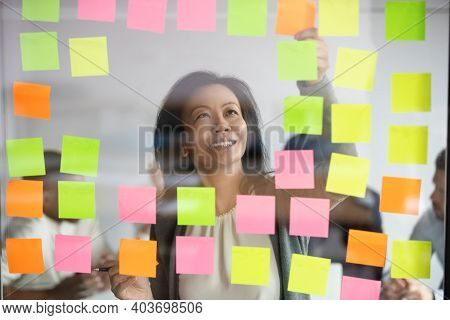 Happy Middle Aged Korean Female Project Manager Organizing Effective Workflow.