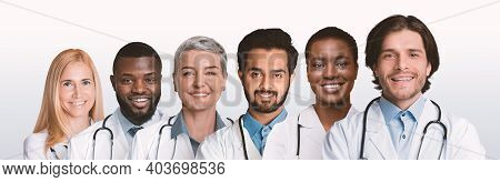 Diverse Professional Doctors In Uniform Standing In A Row Posing Smiling To Camera On White Studio B