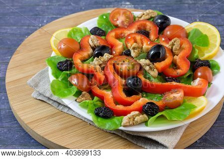 On A White Plate, Vitamin Fresh Vegetable Salad With Lettuce, Red Peppers, Olives, Walnuts, Cherry T