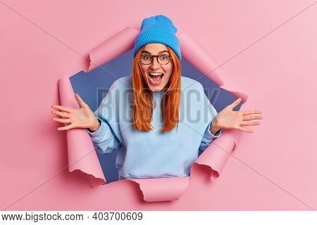 Overemotive Positive Ginger Young Woman Exclaims Loudly Spreads Palms Feels Very Glad Wears Blue Hat