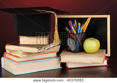 Books and magister cap against school board on wooden table on red background