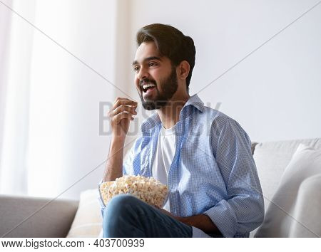 Cheerful Arab Guy Watching Tv And Eating Popcorn At Home, Relaxing On Couch In Living Room, Cheerful