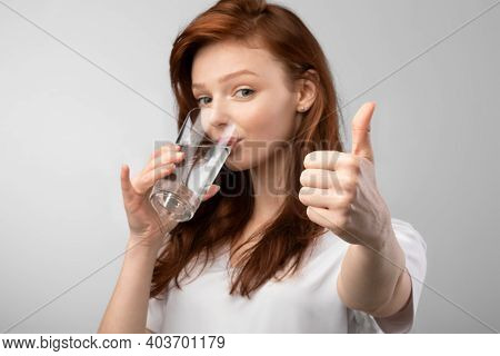 Ginger-haired Young Lady Drinking Glass Of Water And Gesturing Thumbs Up Smiling To Camera Standing