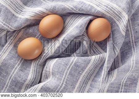 Three Chicken Eggs On A Textile Towel. Gray-blue Background With Eggs