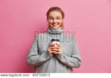 Pretty Smiling Teenage Girl With Glad Expression Holds Disposable Cup Of Coffee Enjoys Drinking Hot