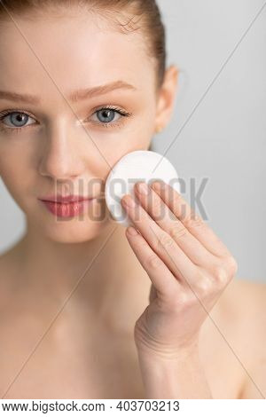 Facial Skincare. Red-haired Teen Girl Cleansing Skin With Cotton Pad Standing Over Gray Studio Backg