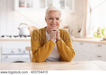 Portrait Of Happy Old Woman Sitting In Cozy Kitchen And Smiling At Camera, Copy Space. Positive Seni