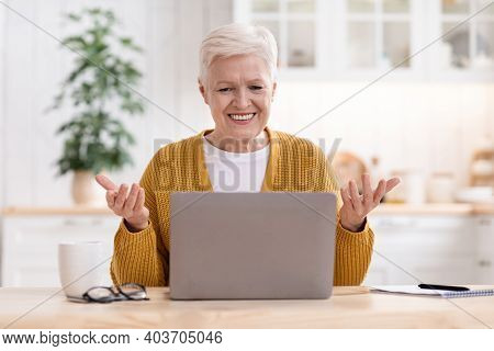 Happy Elegant Old Woman Sitting In Kitchen, Using Modern Laptop And Gesturing, Having Video Call Wit