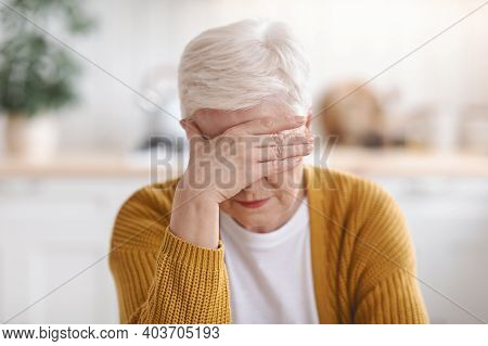 Senior Grey-haired Woman Suffering From Migraine, Touching Her Forehead, Kitchen Interior, Closeup.