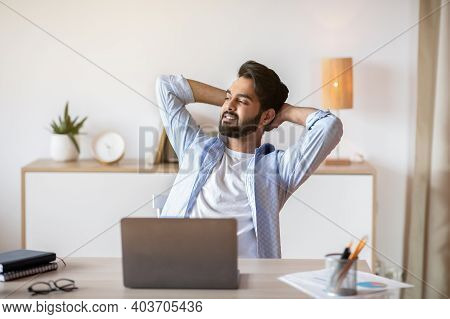 Relaxed Eastern Man Leaning Back In Chair, Resting After Online Work With Laptop, Millennial Arab Gu