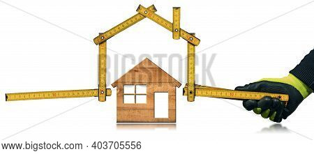 Closeup Of A Hand With Work Glove Holding A Folding Ruler In The Shape Of A House Above A Wooden Mod