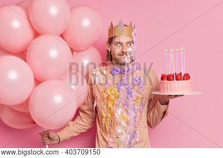 Photo Of Handsome Cheerful European Man Holds Strawberry Cake And Helium Balloons Smeared With Cream