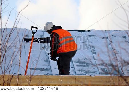 Worker Removing Snow On The Roof Of A Building. Snow Removal, Climber Cleaning Roof In Winter