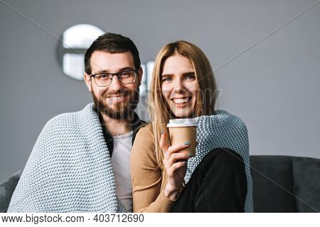 Portrait Of Cheerful Couple Sitting On The Sofa At Home And Looking On Camera.
