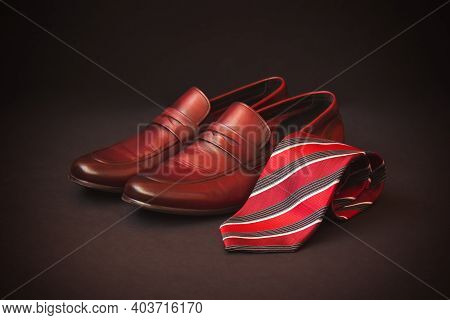 Stylish Red Striped  Rolled  Necktie And Fashionable Brown Men's Shoes On Dark Background. Selective
