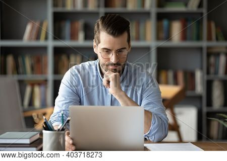 Thoughtful Young 30s Caucasian Businessman Working On Computer.