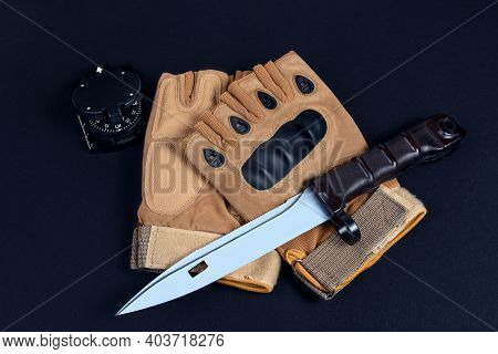 Pair Of Brown Tactical Gloves, Bayonet Knife And Compass On Black Background