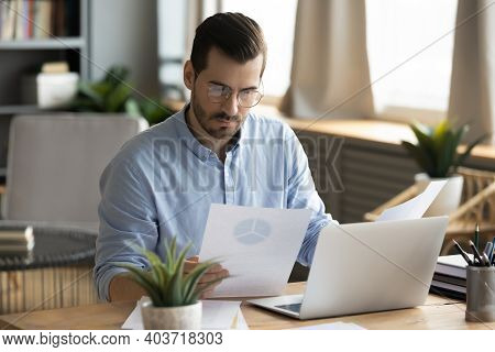Concentrated Young Businessman Analyzing Marketing Research Report.