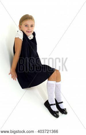 Lovely Girl Posing In Studio On Background. Cheerful Blonde Girl Wearing School Uniform Sitting On F
