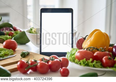 Digital Tablet Computer With Mockup White Screen On Vegetarian Healthy Food Vegetable Background. On