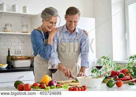 Happy Old Senior 50s Couple Wearing Aprons Having Fun Preparing Meal Salad At Home. Smiling Middle A