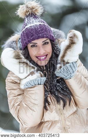 Fashionable Female Model Wears Fluffy Gloves, Shiny Jacket And Violet Pom Pom Hat For Winter.