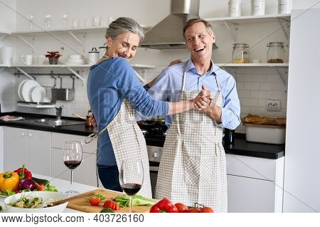 Happy Affectionate Older Middle Aged Couple Laughing, Dancing, Preparing Healthy Meal In Modern Kitc
