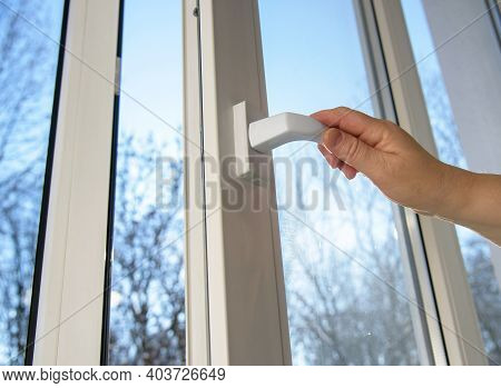 Hand Opens Vinyl Plastic Window On Blue Sky Winter Background. Oneped Window.