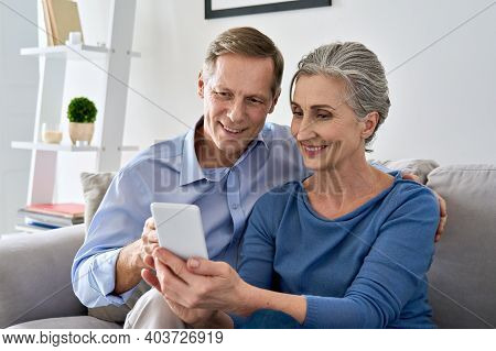 Middle Aged 50s Senior Couple Holding Device Looking At Smartphone Using Mobile Apps Tech, Shopping
