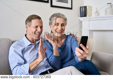 Happy Old Couple Waving Hands Making Online Video Call On Cell Phone. Mature Retired 50s Grandparent