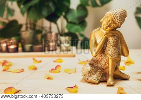 Golden Bronze Buddha Decorative Statuette With Flower Petals On Wooden Table With Burnig Candles, Mo