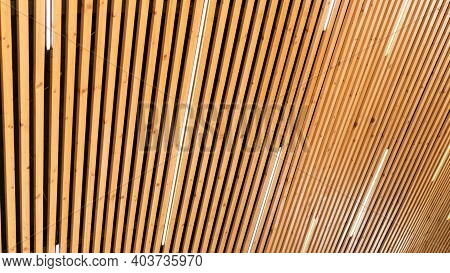Close-up On A Ceiling Made Of Wooden Planks With Led Strip Lamps. The Texture Of Wooden Boards. Idea