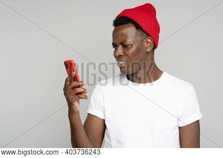Confused African Millennial Hipster Man Looking At Smartphone, Annoyed By Spam, Intrusive Adware, Un