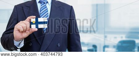 Cropped Image Of Businessman Holding Plastic Credit Card With Printed Flag Of Finland. Background Bl