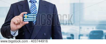 Cropped Image Of Businessman Holding Plastic Credit Card With Printed Flag Of Greece. Background Blu