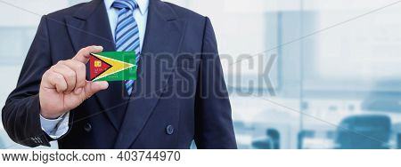 Cropped Image Of Businessman Holding Plastic Credit Card With Printed Flag Of Guyana. Background Blu