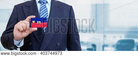 Cropped Image Of Businessman Holding Plastic Credit Card With Printed Flag Of Haiti. Background Blur