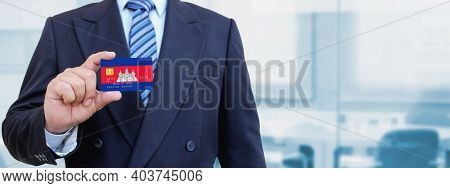 Cropped Image Of Businessman Holding Plastic Credit Card With Printed Flag Of Cambodia. Background B