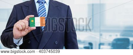 Cropped Image Of Businessman Holding Plastic Credit Card With Printed Flag Of Ireland. Background Bl