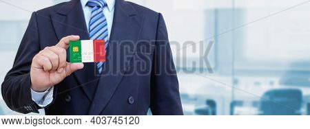 Cropped Image Of Businessman Holding Plastic Credit Card With Printed Flag Of Italy. Background Blur