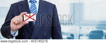 Cropped Image Of Businessman Holding Plastic Credit Card With Printed Flag Of Jersey. Background Blu